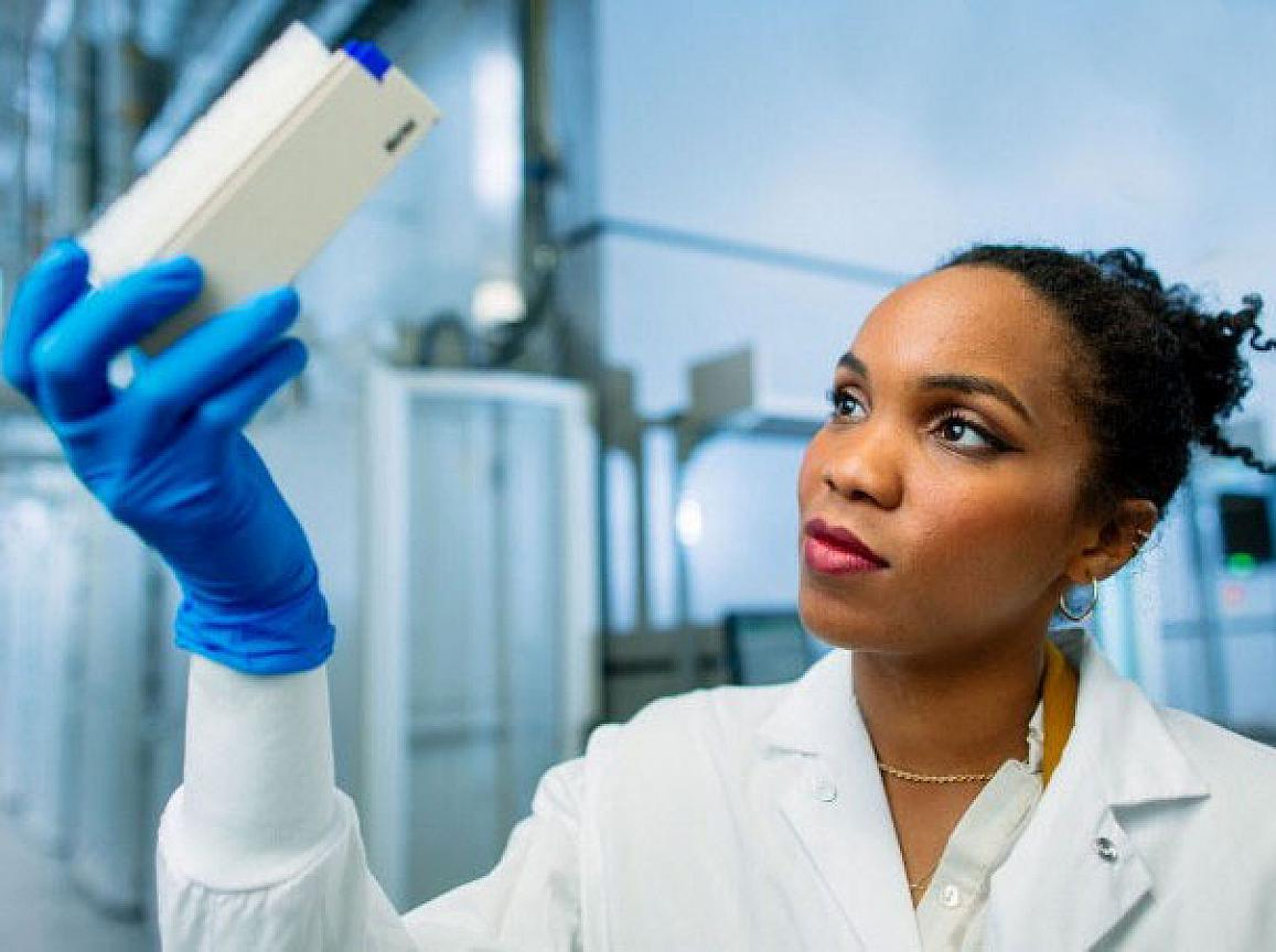 Female researcher holding test tubes with blue gloves