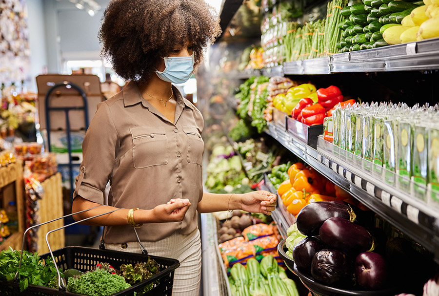 Woman wearing a protective face mask looking at fresh produce in a supermarket