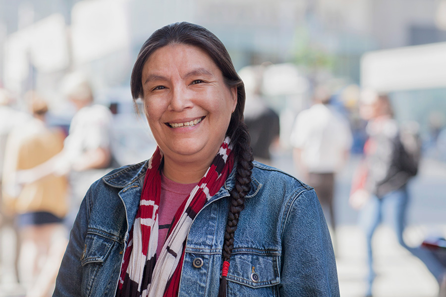 Native American woman stands smiling on a city street